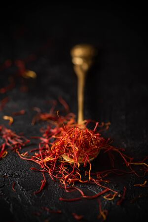 Saffron spices threads in vintage brass spoon on black slate stone table. Saffron flavor and coloring seasoning ingredient. Standard-Bild