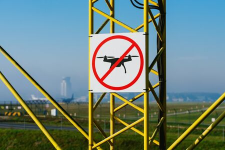 No drone zone sign on approach lighting system at airport runway.