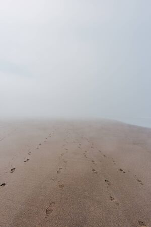 Ocean beach in dense fog with footprints on sand leading nowhere