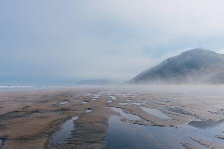 Beautiful foggy ocean beach in winter Stock fotó