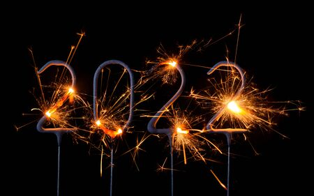 Happy New Year 2022. Digits of year 2022 made by burning sparklers isolated on black background.