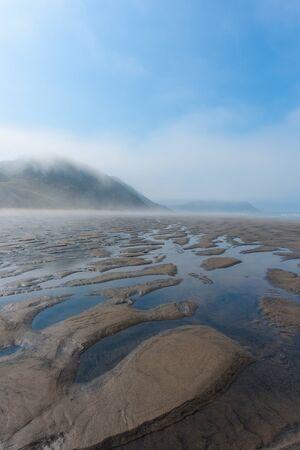 Wde sandy beach in the fog during ebb