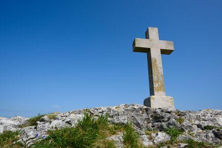 Christian cross on rock over blue sky as copy-space
