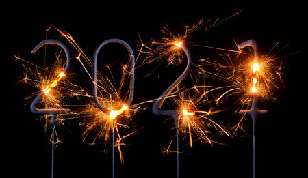 Happy New Year 2021. Digits of year 2021 made by burning sparklers isolated on black background.