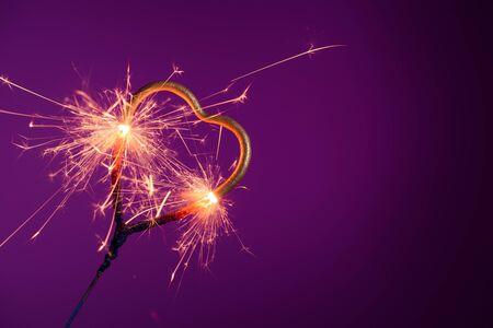 Burning sparkler in shape of heart. Wedding love Valentines day invitation banner with copy-space.