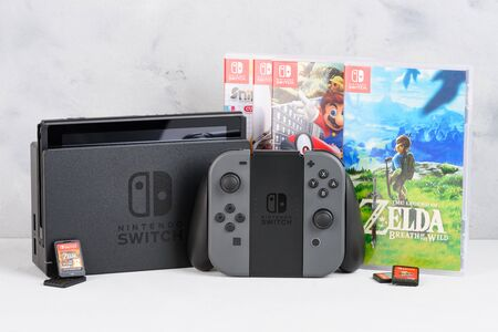 Krakow, Poland - Januray  14, 2020: Nintendo Switch gaming console with popular Zelda and Mario games and game cards still-life.
