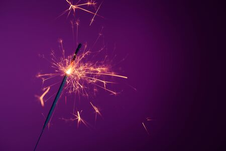 Shiny bright burning bengal fire party sparkler on purple background with copy-space Stock fotó