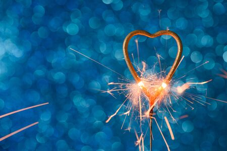 Sparkler in a shape of golden heat burning over blue bokeh background with copy-space. Wedding or Valentines day invitation card concept. Stock fotó