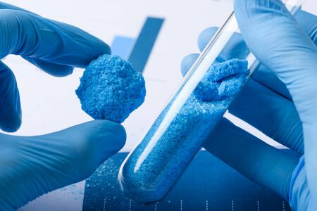 Researcher show blue crystal material in hand and glass test tube in laboratory