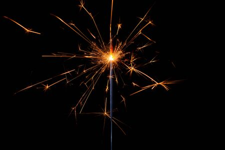 Shiny sparkler with lots of sparks burning bright isolated on black background.