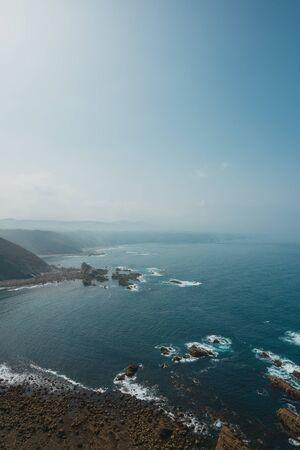 Rocky ocean coast with big stones in water Stock fotó