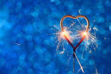 Love wedding valentines day party bengal fire. Burning sparkler heart shaped on blue bokeh background.
