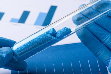Scientist hold test tube with blue crystals in laboratory
