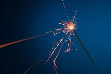 Bright burning party sparkler bengal fire on blue background
