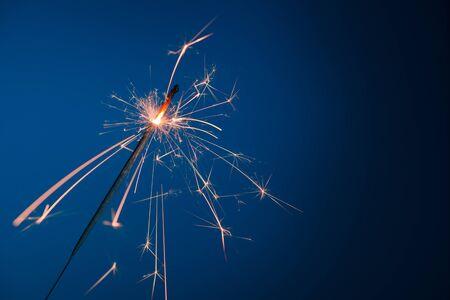 Bright burning sparkler bengal fire on blue background Stock fotó
