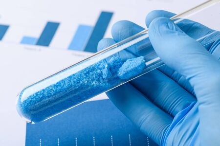 Scientist hold glass test tube with blue crystals in lab