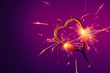 Golden heart shaped sparkler burning bright with sparks Stock fotó