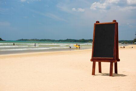 Blank wooden chalkboard blackboard stand in sand on tropical beach