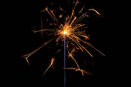 Sparkler with lots of sparks burning bright isolated on black background. Stock fotó