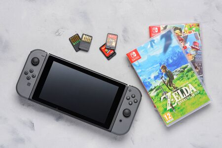 Krakow, Poland - Januray  14, 2020:  Switch gaming console with popular Zelda and Mario games and game cards flat lay on table. Illustrative editorial.