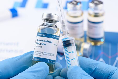 Coronavirus COVID-19 vaccine vial and injection syringe in scientist hands concept. Research for new novel corona virus immunization drug.