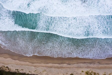 Ocean beach with blue waves aerial drone top view