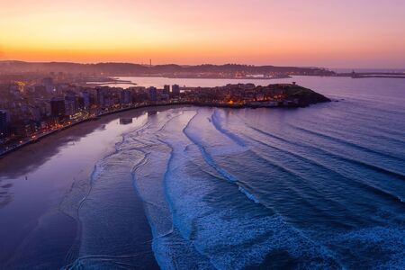 Gijon downtown and San Lorenzo beach aerial drone view at twilight. Gijón or Xixón is the biggest city in Asturias Spain.
