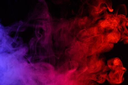 Colored smoke clouds flowing dark abstract background