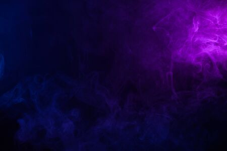 Soft clouds of colorful smoke on dark background Imagens