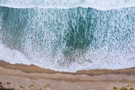 Sand dunes on the beach and ocean waves aerial drone top view