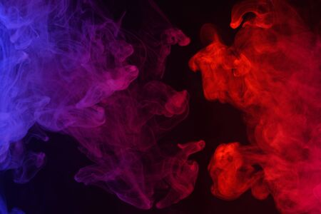 Multicolored smoke clouds flowing dark abstract background