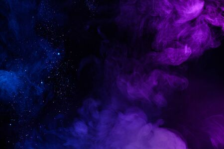 Shiny glitter in clouds of pink and blue fog smoke abstract background
