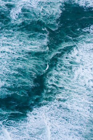 Blue foamy ocean waves and sand aerial drone top view