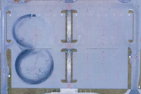 Car drift skid marks on empty parking lot aerial drone top view