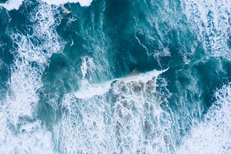 Blue ocean waves and sand aerial drone top view