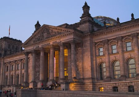 The Reichstag building of Berlin, night view. Reichstag is a residence of German Parliament. There are tourists on the stairs waiting to visit glass dome on the top of reichstag. Фото со стока
