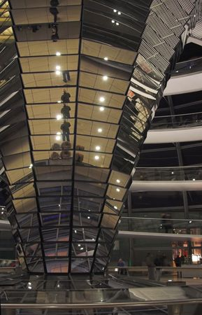 Interior of Reichstag glass dome at night. The central pillar decorated with mirrors and fragment of spiral ramp are shown. Reichstag is a residence of German Parliament - Bundestag.
