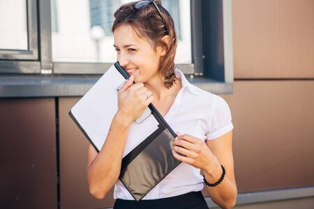 beautiful businesswoman with a folder in front of modern office