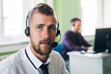 현대 사무실에서 사업가 헤드셋과 전화로 카메라를 찾고