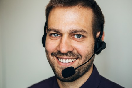 helping up: Close up of smiling call center agent helping costumer on white background