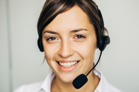 handsfree telephone: Closeup of a beautiful business customer service woman smiling on white background Stock Photo