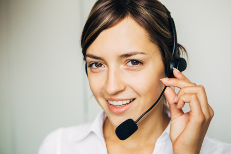 Closeup of a beautiful business customer service woman smiling on white background Stock Photo
