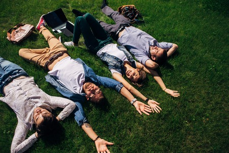four students lying on the grass near the University Stock Photo
