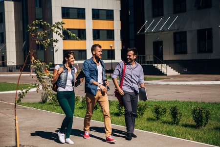 slow motion: three students walking on campus at the university,slow motion