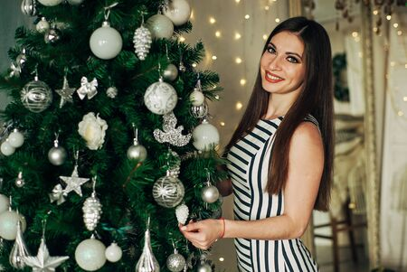 Beautiful brunette young woman in green dress decorating a Christmas tree Stock Photo