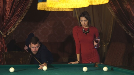 Beautiful happy couple playing billiards,beautiful woman in a red dress watching the game men in Billiards Stock Photo