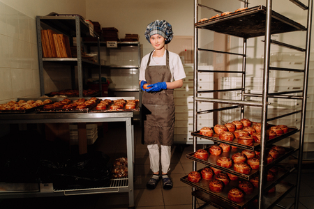 cinnamon swirl: Baker smiling at camera holding rack of rolls in a commercial kitchen Stock Photo