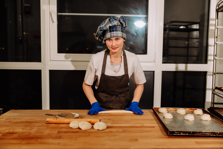 cake factory: Woman bake pies. Confectioners make desserts. Making buns. Dough on the table. Knead the dough. Stock Photo