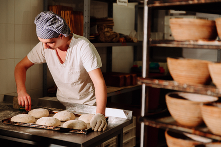 makes: a Baker makes manual incisions on the dough for the bread