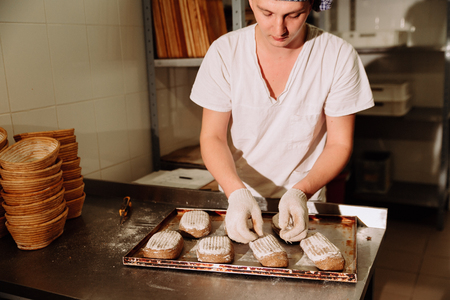 Proving dough of bran in basket. Private Bakery. Production bread. Workshop making Foto de archivo